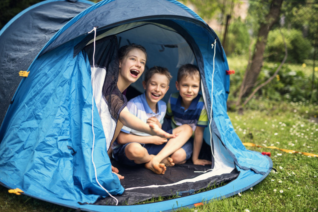 Kids playing camping in tent in garden