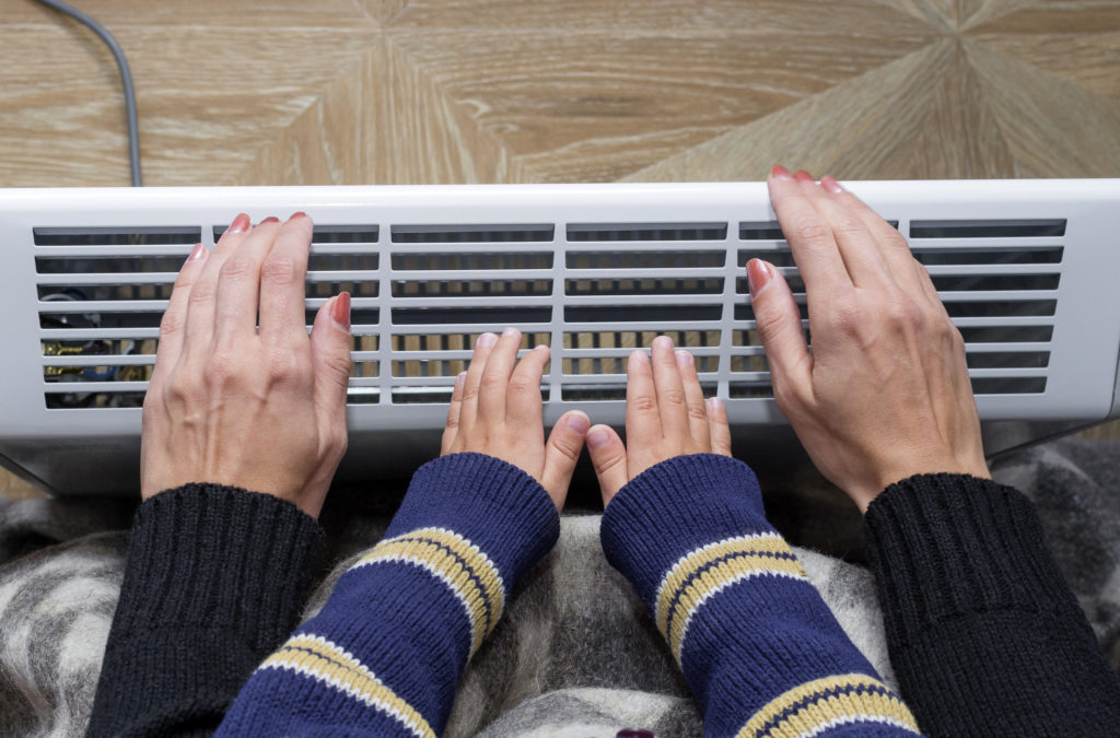 Mother and son heating up a hand in front of an electric heater