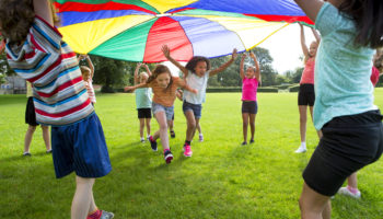 hildren playing a game with a colourful Parachute
