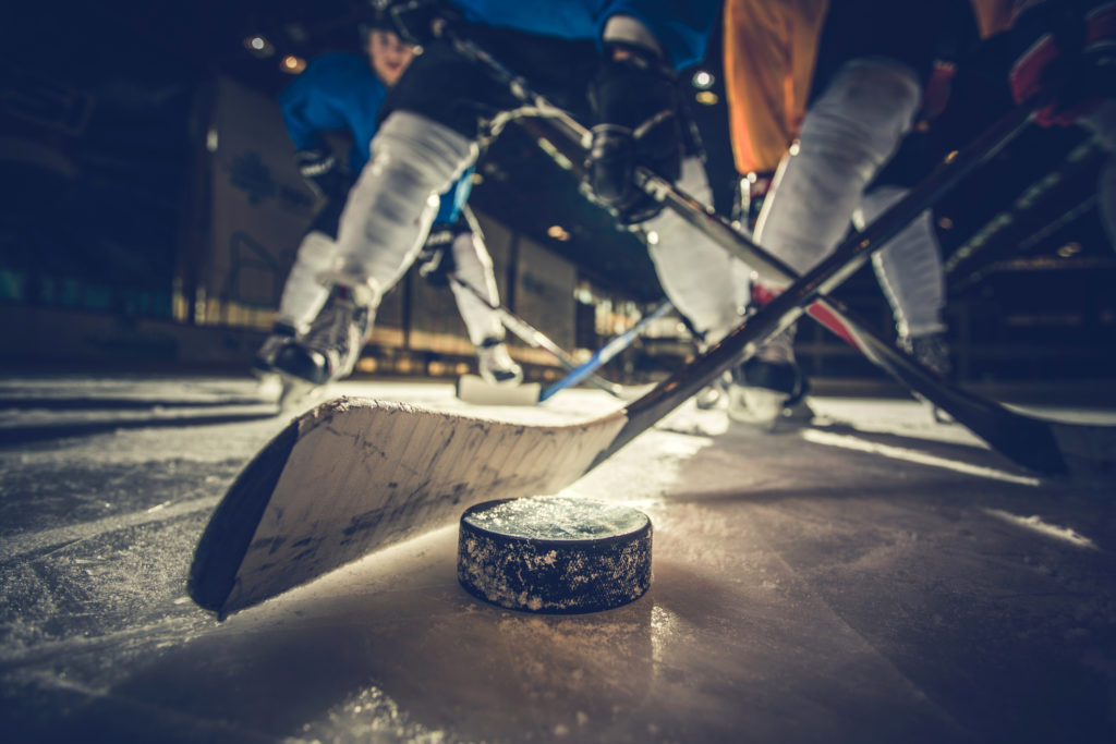 Close up of ice hockey puck and stick during a match.