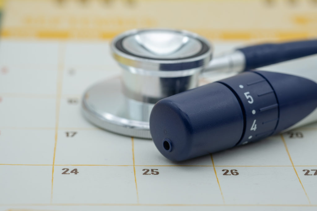 People, diabetes and healthcare concept. Close up of lancet for check blood sugar level with Stethoscope on calendar.