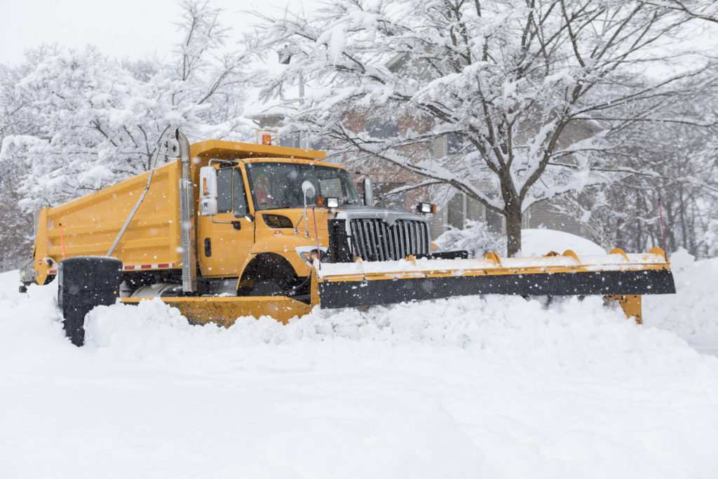 The snow plow is clearing the residential street after a snow storm. There is a large amount of heavy snow to plow off the road leaving a big snow bank along side the curb.