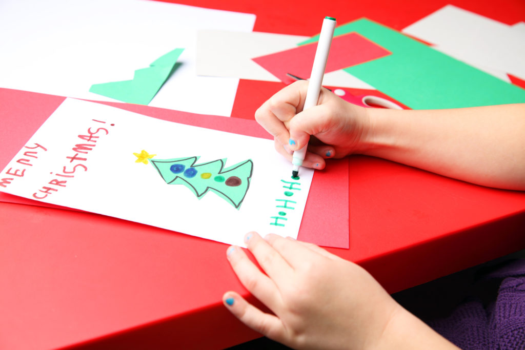 A young girl makes the finishing touches to her Christmas card. Merry Christmas!