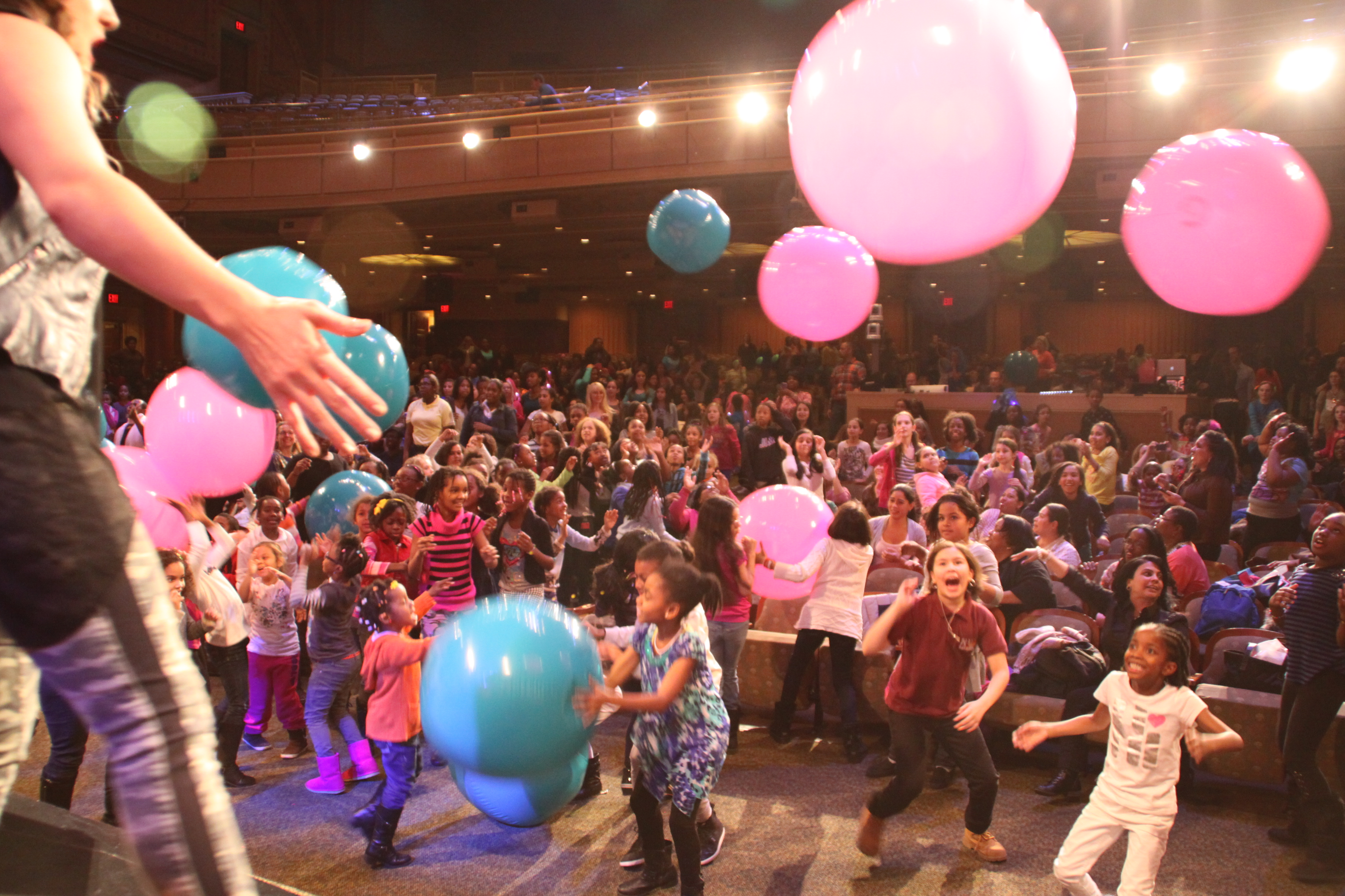 Girls and their moms playing with balloons in an auditorium
