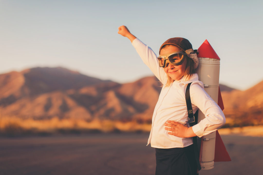 A young girl businesswoman or student dressed in business attire looks to the distance while wearing a rocket strapped to her back and a flying cap and goggles. She is standing on a country road among the mountains of Utah, USA. She is confident in her abilities to lead her business and obtain her goals.