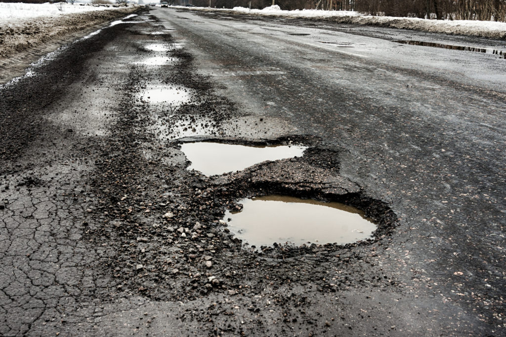 old highway with holes and snow. Landscape road potholes in cloudy winter weather. concept absence of timely repair of highway.