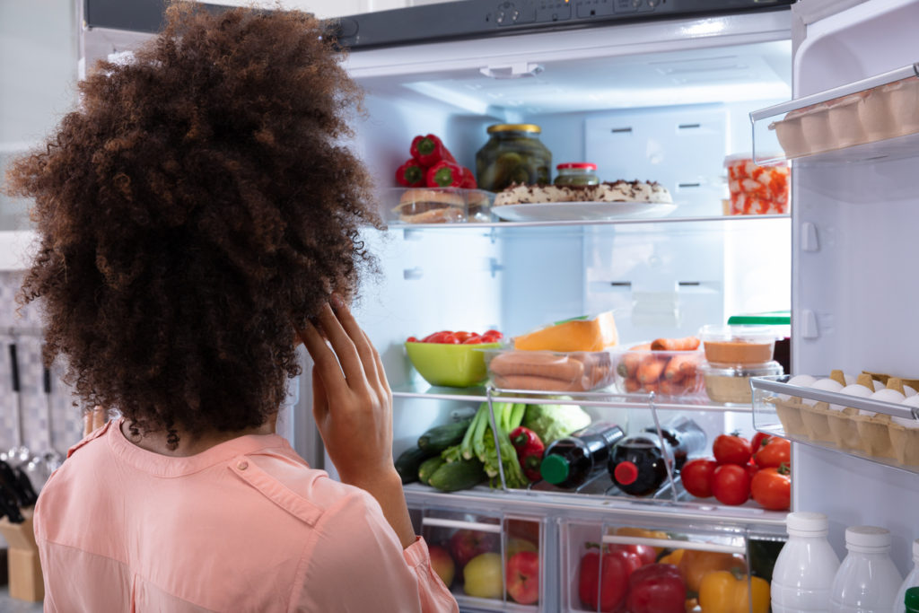 Rear View Of A Confused Woman Searching For Food In An Open Refrigerator
