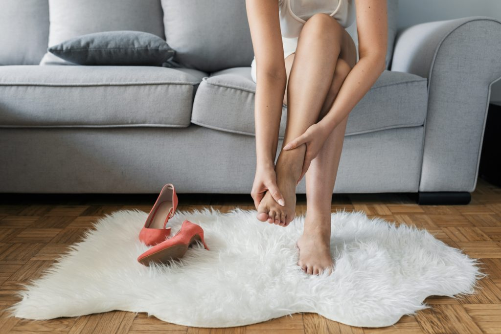 Closeup of hands massaging swollen foot while sitting on sofa during the day at home. Photo of Young Unrecognizable Caucasian woman suffering from pain in leg. Woman massaging her legs after wearing high heels all day at work in office