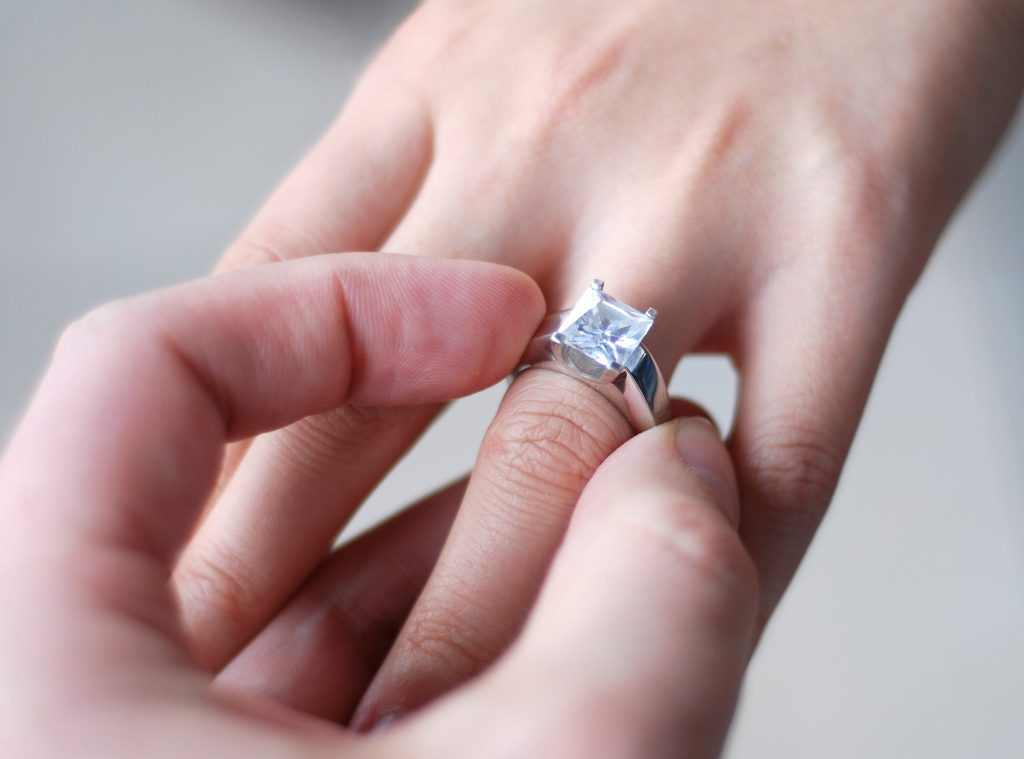 Close up of a man placing a diamond engagement ring on a woman's finger.Wedding related images