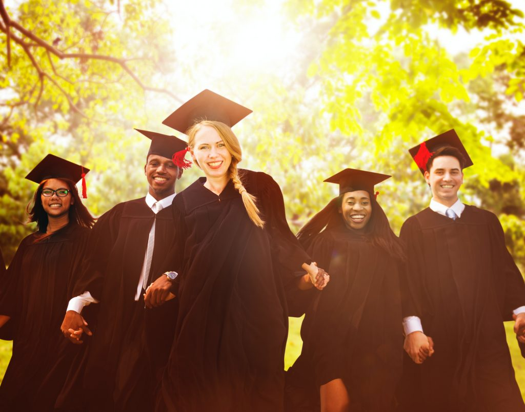 Graduates holding hands in caps and gowns
