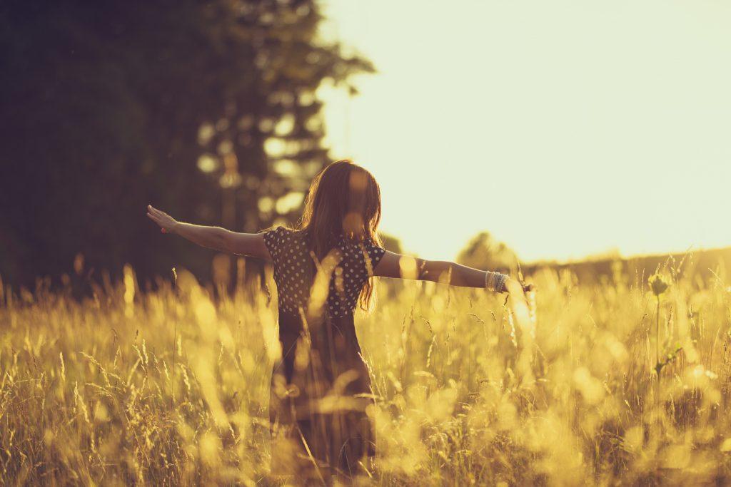 a young women walk through the high grass. the evening sun is shining very bright