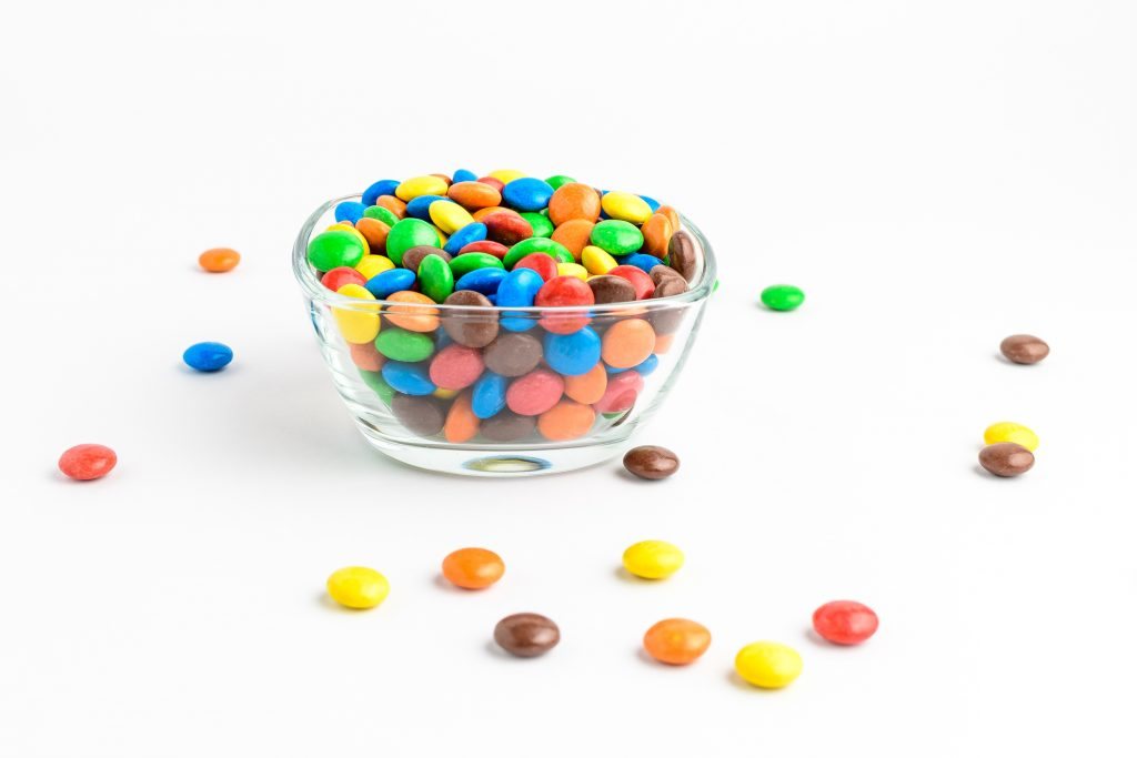 Group of small mixed colored chocolate coated candies in a transparent glass bowl on a table, isolated on white background, side view photo of yellow, orange, green, red and brown sweets